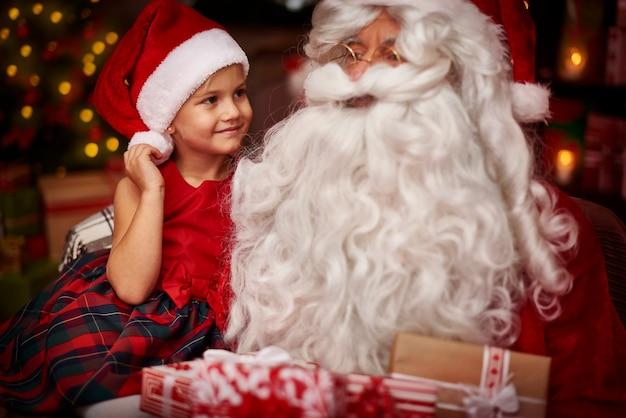Leuk meisje, zittend op de knieën van de kerstman