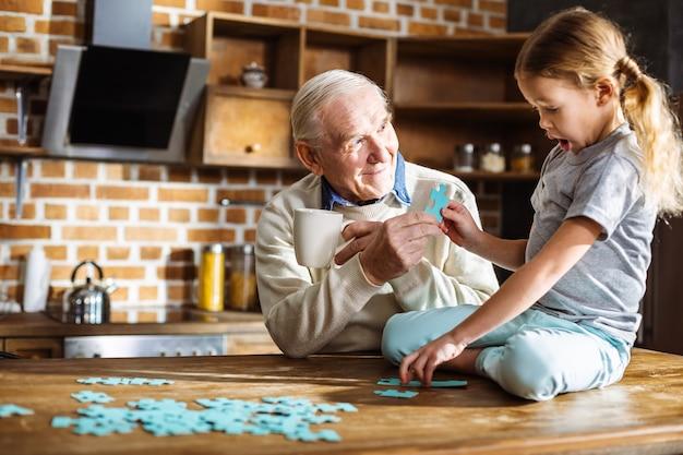 Leuk meisje zittend op de tafel tijdens het samenstellen van een puzzel met haar grootvader