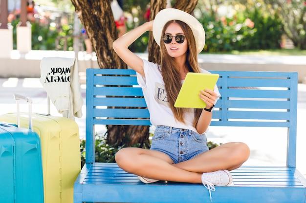 Leuk meisje zittend op een blauwe bank en spelen op een tablet in geel geval.