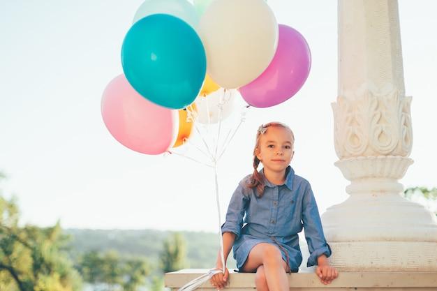 Leuk meisjesportret die kleurrijke ballons in het stadspark houden