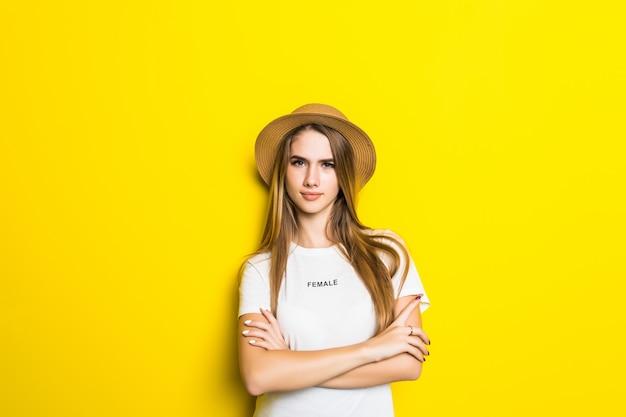 Leuk model in wit t-shirt en hoed onder oranje achtergrond met grappig gezicht