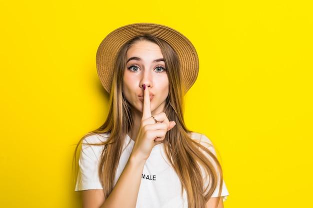 Leuk model in wit t-shirt en hoed onder oranje achtergrond met vinger op lippen