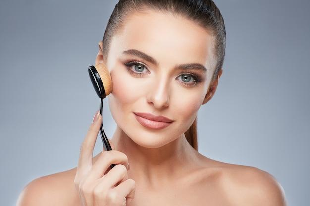 Leuk model met bruin haar gefixeerd achter, schone frisse huid, grote ogen en blote schouders poseren bij grijze studio achtergrond en camera kijken, close-up, make-up borstel vasthouden.