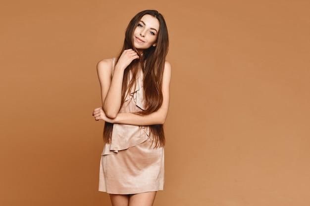 Leuk modelmeisje met perfect lichaam in een korte beige jurk die zich voordeed op het beige oppervlak studio-opname met kopie ruimte aan beide kanten