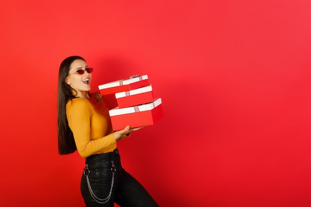 Leuk modieus meisje dat in gele blouse en rode glazen stapel giftdozen houdt die over rood oppervlak met exemplaarruimte worden geïsoleerd.