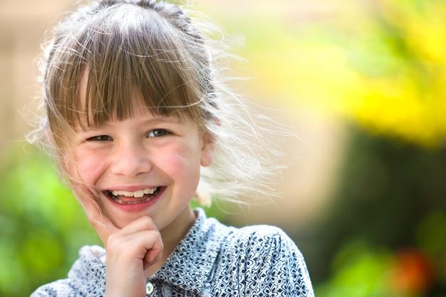 Leuk mooi kindmeisje met grijze ogen en het eerlijke haar glimlachen