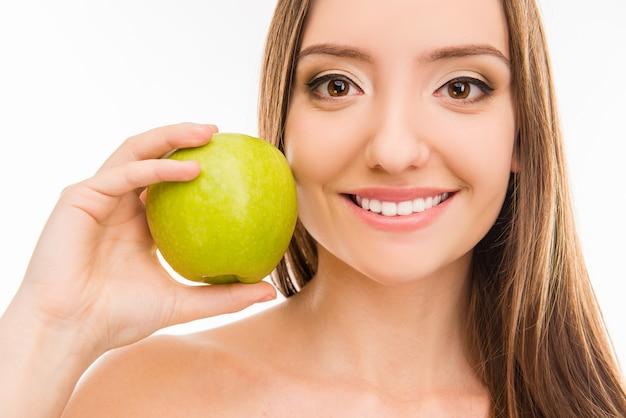 Leuk mooi meisje dat haar witte glimlach met groene appel toont