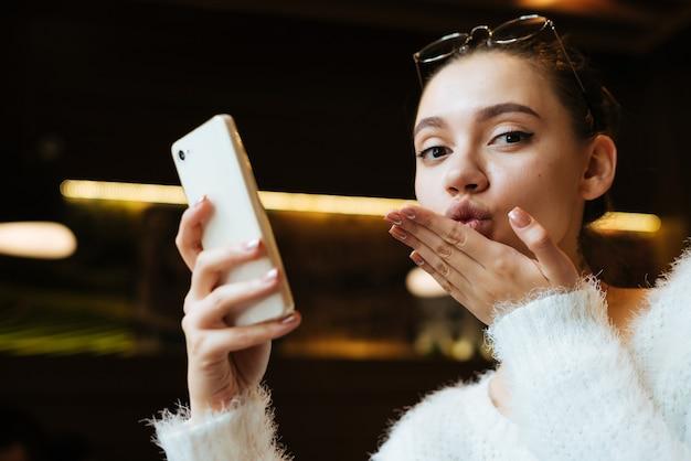 Leuk mooi meisje dat in café zit, smartphone vasthoudt en aan werk denkt