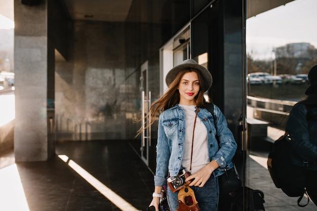 Leuk mooi meisje in hoed met mooie gezichtsuitdrukking poseren buiten terwijl wind spelen met haar haren alvorens te winkelen.