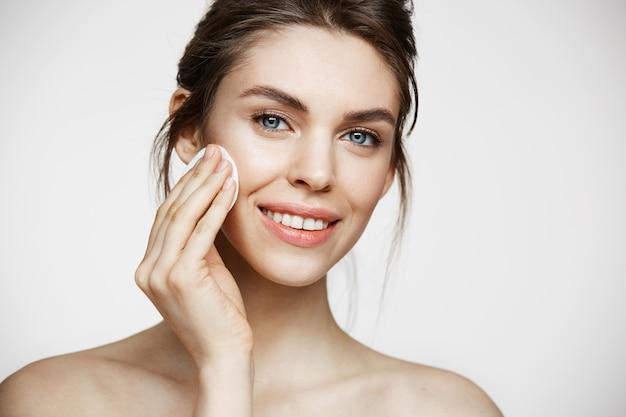 Leuk mooi natuurlijk donkerbruin meisjes schoonmakend gezicht met het katoenen spons glimlachen die camera over witte achtergrond bekijken. cosmetologie en spa.