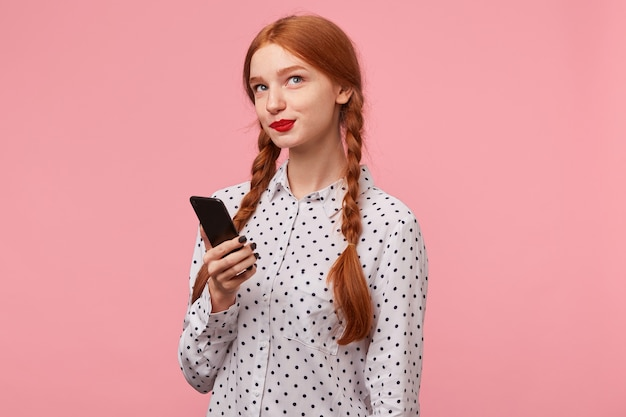 Leuk mooi roodharig meisje met een telefoon op haar hand ziet er koket mysterieus uit in de rechterbovenhoek, denkt na wat ze haar vriend moet schrijven in een bericht, geïsoleerd op een roze
