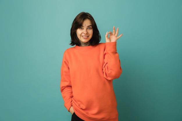 Leuk, oké. portret van de blanke vrouw geïsoleerd op blauwe muur met copyspace. mooi vrouwelijk model in oranje hoodie. concept van menselijke emoties, gezichtsuitdrukking