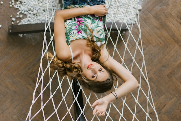 Leuk op een hangmat liggen, en meisje die rusten glimlachen
