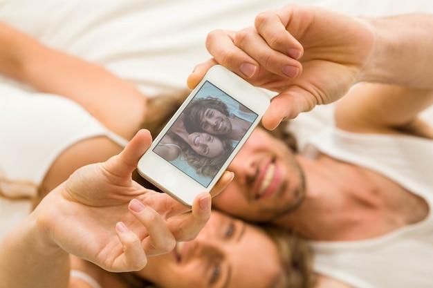 Leuk paar dat een selfie neemt die op hun bed ligt