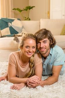 Leuk paar dat op het tapijt in de woonkamer ligt