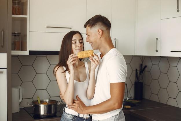 Leuk paar in een keuken. dame in een wit t-shirt. paar eten thuis gekookte maïs.