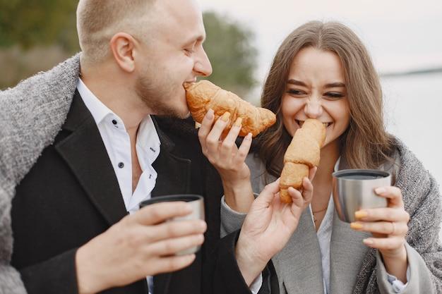 Leuk paar in een park. dame in een grijze jas. mensen met een thermoskan en een croissant.