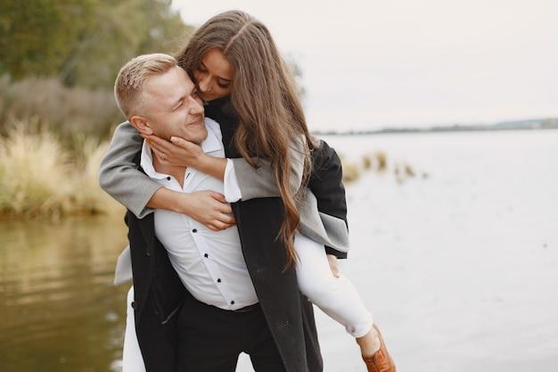 Leuk paar in een park. dame in een grijze jas. mensen op de pier.