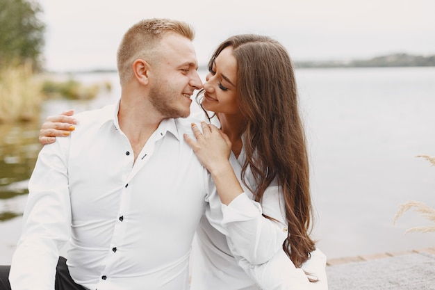 Leuk paar in een park. dame in een wit overhemd. mensen op de pier.