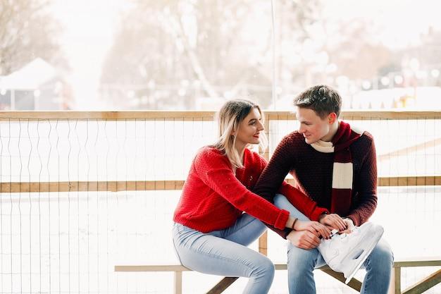 Leuk paar in een rode truien helpen elkaar om te schaatsen