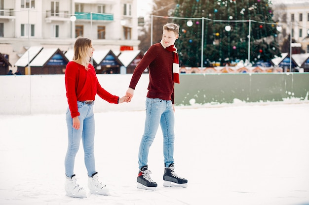 Leuk paar in rode sweaters die pret in een ijsarena hebben