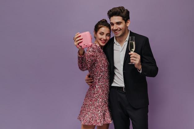 Leuk paar jonge mensen die in feestoutfits staan, glimlachen en selfie maken tegen een lichtpaarse muur