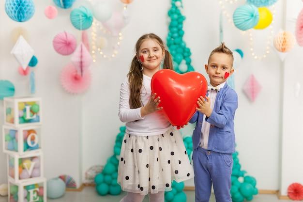 Leuk paar kinderen met rode hartballon. valentijnsdag en liefde concept, studio-opname