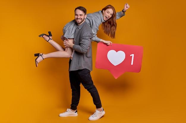 Leuk paar man vrouw poseren met als teken in hartvorm geïsoleerd op een oranje achtergrond.
