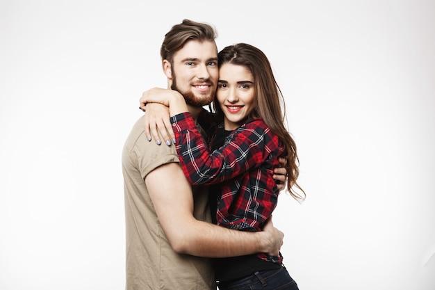 Leuk paar omhelzen elkaar en kijken naar de camera