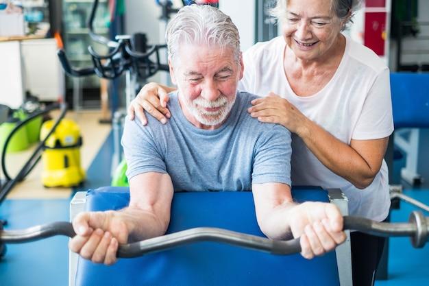 Leuk paar van twee seniros in de sportschool die oefeningen doen - man met een barr met gewicht terwijl zijn vrouw hem helpt en ernaar kijkt