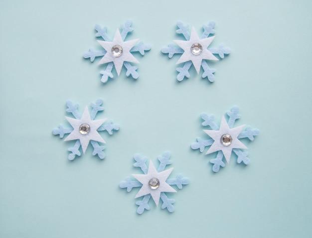 Leuk patroon van blauwe sneeuwvlokken gemaakt van vilt en strass steentjes op een blauwe kerst achtergrond, bovenaanzicht, plat leggen, kopie van de ruimte.