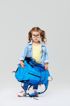 Leuk peuter meisje met een blauwe rugzak op haar rug, met een wereldbol in haar handen