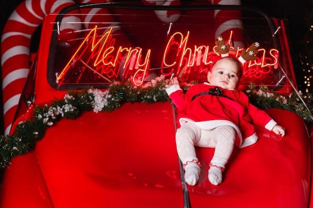 Leuk peutermeisje met in hertengeweien die op retro rode auto bij kerstmisstudio liggen. kopieer ruimte. trouwen met kerstmis op de achtergrond.