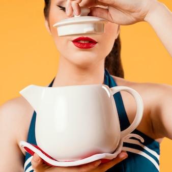 Leuk pinupmeisje dat een theepot houdt