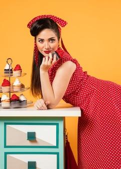 Leuk pinupmeisje dat zich naast sommige cupcakes bevindt