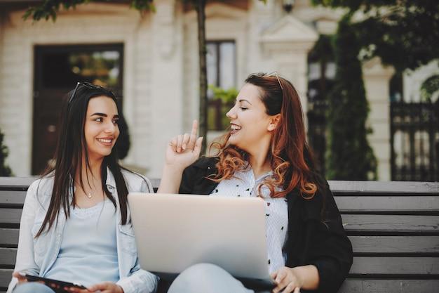 Leuk plus size meisje met rood haar dat met haar vriendin spreekt terwijl ze iets met een vinger laat zien terwijl een ander haar glimlachend tegen een gebouw kijkt.