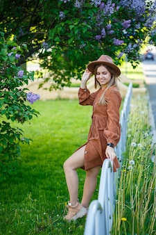 Leuk portret van een meisje met een bruine hoed op een lila achtergrond in een botanische tuin. lang blond haar ligt op de schouders