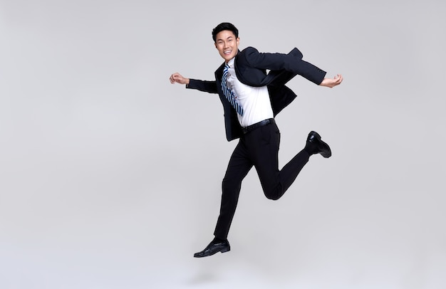 Leuk portret van gelukkige energieke jonge aziatische zakenman springen in de lucht op studio wit.