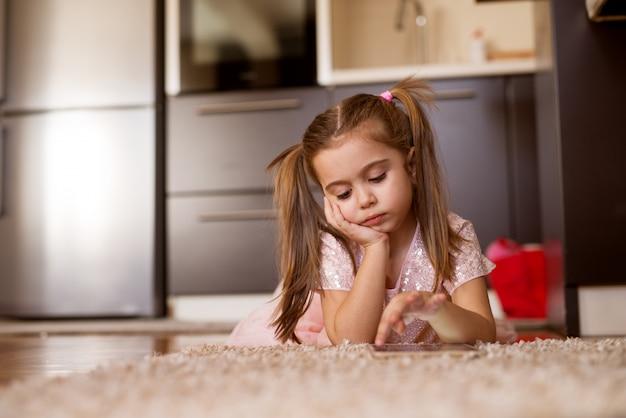 Leuk portret van weinig meisje die van het peuterkind op een tapijt liggen terwijl wat betreft een tablet.