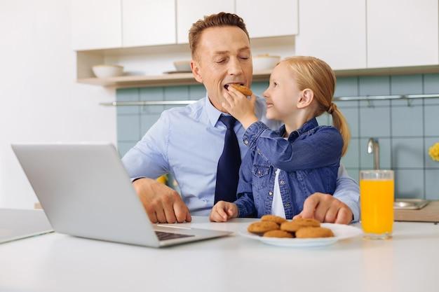 Leuk positief gelukkig meisje dat haar vader bekijkt en glimlacht terwijl hij met een koekje voedt