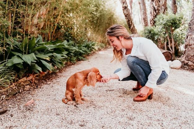 Leuk puppy die van cocker-spaniëlhond poot geven aan haar eigenaar in een park