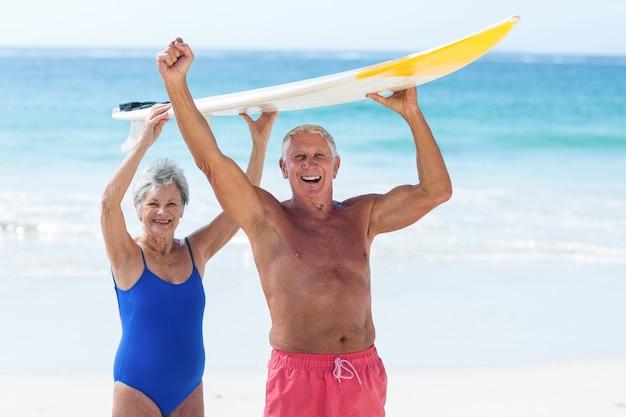 Leuk rijp paar dat een surfplank boven hun hoofd houdt