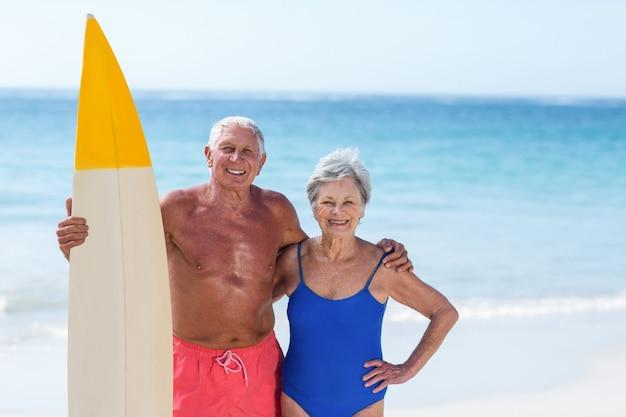 Leuk rijp paar dat een surfplank houdt