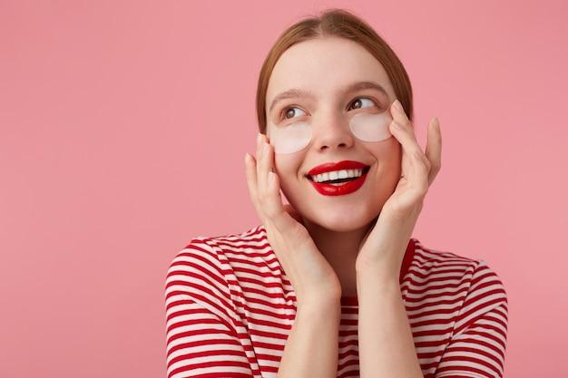 Leuk roodharig meisje in een rood gestreept t-shirt, met rode lippen, raakt zijn gezicht met vingers aan, kijkt dromerig in de verte en bereidt zich voor op een date met zijn geliefde. staat.