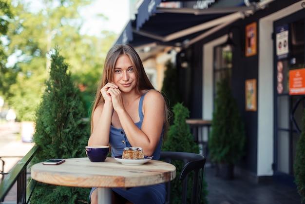 Leuk schattig meisje glimlacht over een kopje thee. stijlvolle blauwe top met een rokje. groene thuja's in een café.