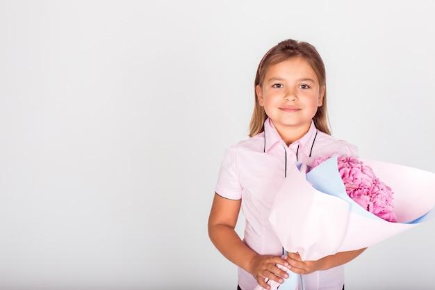 Leuk schattig meisje met een boeket roze bloemen voor schoolleraar van mooie moeder.