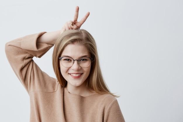 Leuk schattig vrouwelijk model in bril ziet er vreugdevol uit, gebaren met vingers, heeft een gelukkige uitdrukking, poseert met kopie ruimte. vrij blond meisje dat pret heeft