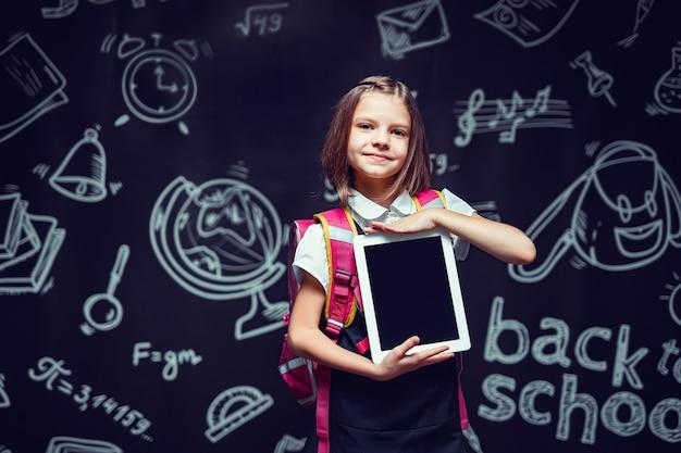 Leuk schoolmeisje dat zich voorbereidt om naar school te gaan met een rugzak die de tablet terug naar schoolconcept laat zien
