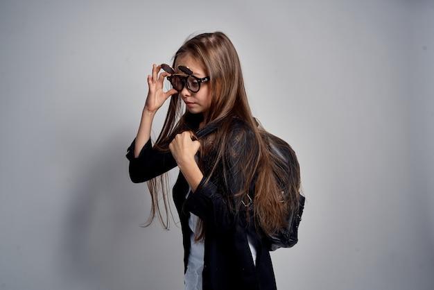 Leuk schoolmeisje dat zonnebril op grijs draagt