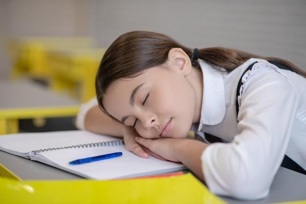 Leuk schoolmeisje met gesloten ogen die het hoofd op haar handen en op het bureau rusten dat op school moe wordt